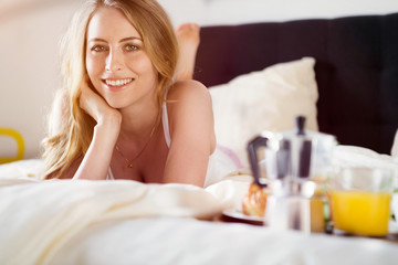 Woman having breakfast in bed. hotel service