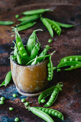 Bunch of mature pods of green peas on the old background in rustic style.
