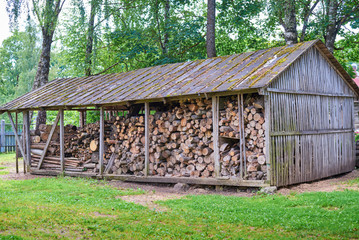 old wooden barn with firewood and a ladder