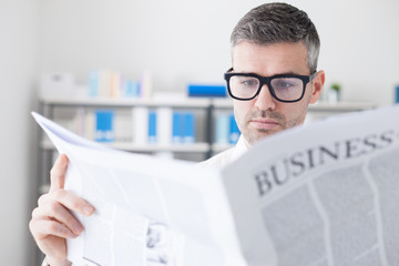 Confident businessman reading a newspaper