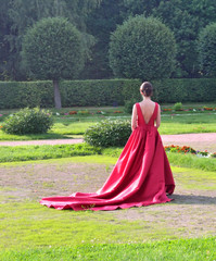 girl in a red ball gown standing by the tree in the park
