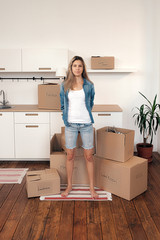 Young blonde girl in casual clothes moving in new home