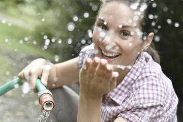 Woman spreading water from garden hose
