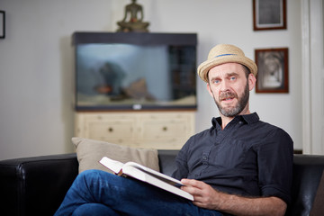 Hipster sitting on leather couch with book looking to camera