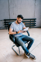 Bearded man reading notebook on chair
