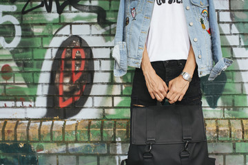 Young man in jeans jacket holding black bag