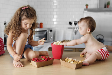 Little girl and her baby brother having snack together on the kitchen counter