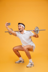 Happy man athlete working out with barbell and making selfie