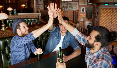 men with beer making high five at bar or pub