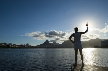 Silhouette of torchbearer athlete standing with sport torch against the setting sun of the Rio de Janeiro Brazil skyline at Lagoa Rodrigo de Freitas lagoon