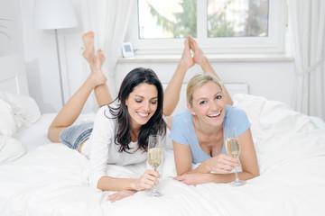 zwei Freundinnen auf einem Bett