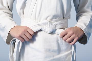 Photo sur Aluminium Combat Teenage's hands tightening white belt on a kimono