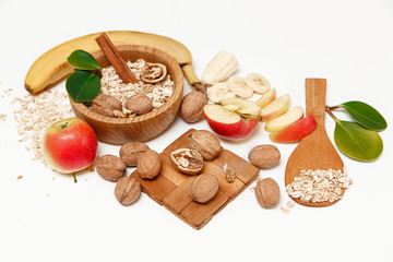 There are Banana,Apple, Walnuts in the Wooden Plate and Rolled Oats,Wooden Spoon,Trivet,with Green Leaves,Healthy Fresh Organic Food on the White Background