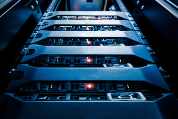 Computer Server mount on rack in data center room with red lighting alarm..