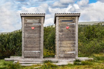 Two wooden outhouse toilets with red heart in mountain landscape.