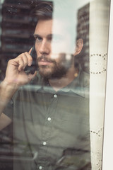 Man standing in front of window and talking on the phone