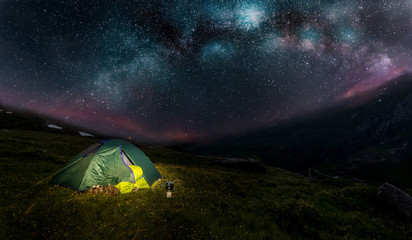 Wild camping in the Alps, people sleeping under a starry sky with Milky Way galaxy