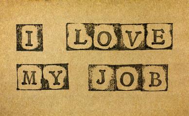 Words I Love My Job make by black alphabet stamps on cardboard.