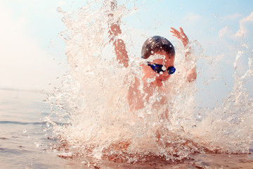 kid dives into the water. splashes of water around a swimmer diving into the water. kid excited about swimming. the concept of a happy childhood Fototapete