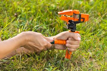 hands installing garden sprinkler for irrigation of lawn