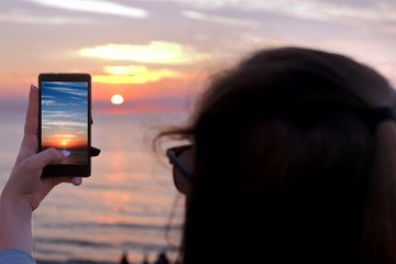 Young girl takes a picture of the sunset by smart phone