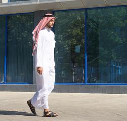 Handsome arabian man walking along the street