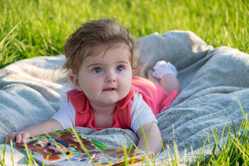 Little girl (six months old) with beautiful blue eyes is looking at pictures in the book. She lies on the grass in the park.