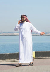 Arabian man talking on the cell phone in the port