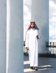 Portrait of a handsome arabian man walking among the columns
