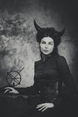 Black and white retro photo, woman demon, devil. Girl with horns, effect of toning