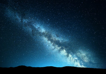 Wall Mural - Night landscape with amazing Milky Way at mountains. Blue night starry sky with hills at summer. Beautiful Galaxy. Universe. Space background