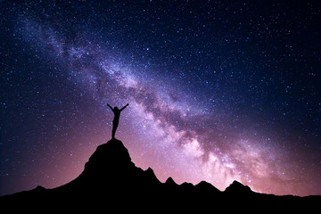 Landscape with vibrant Milky Way. Colorful night sky with stars and silhouette of a standing sporty girl with raised-up arms on the mountain peak on the background of beautiful galaxy.