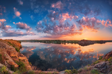 Beautiful panoramic landscape with colorful cloudy sky, lake and mountains. Summer sunset at the river with clouds reflected in water. Panorama. Nature background 壁紙(ウォールミューラル)