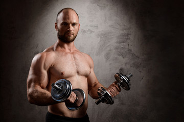 Young powerful sportsman training with dumbbells over dark background.
