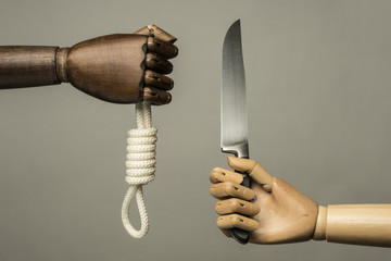 Two methods to commit suicide: the rope or the knife. On gray background. With copy text.