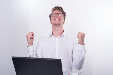 young business man cheering his success while working on laptop