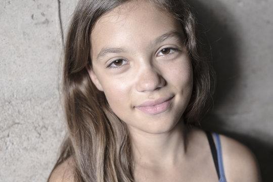 girl's portrai against a gray concrete wall