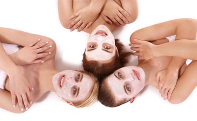 Young beautiful women relaxing with facial masks, top view