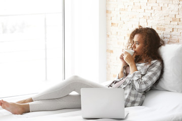 African American woman with a cup of coffee working on computer