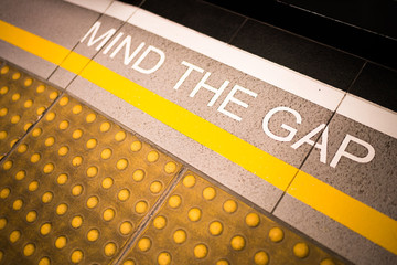Mind the gap sign painted on train station's platform edge, conceptual, vignette darken edge, depth of field blur on far end