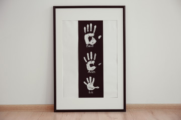 Family hand prints in frame on floor