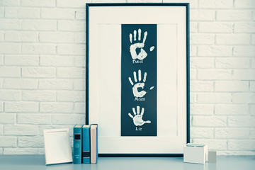 Family hand prints in frame and decor on brick wall background