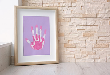 Family hand prints in frame on brick wall background