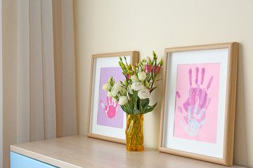 Family hand prints in frames and bouquet in vase on table