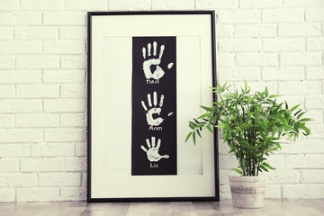 Family hand prints in frame and home plant on floor