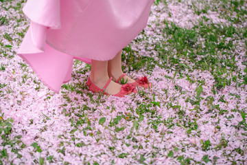 Feet of small girl on grass with petals