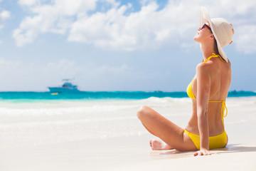 young woman in bikini and sunglasses on tropical beach