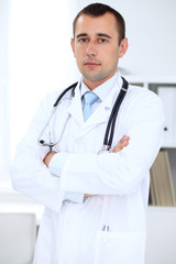 Friendly male doctor in the hospital office. Ready to examine and help patients. High level and quality medical service concept.