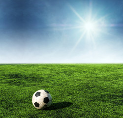 Soccer ball on green grass at soccer field with sunshine on blue sky