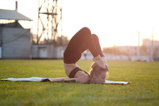 Young woman in black sportswear doing yoga on green grass